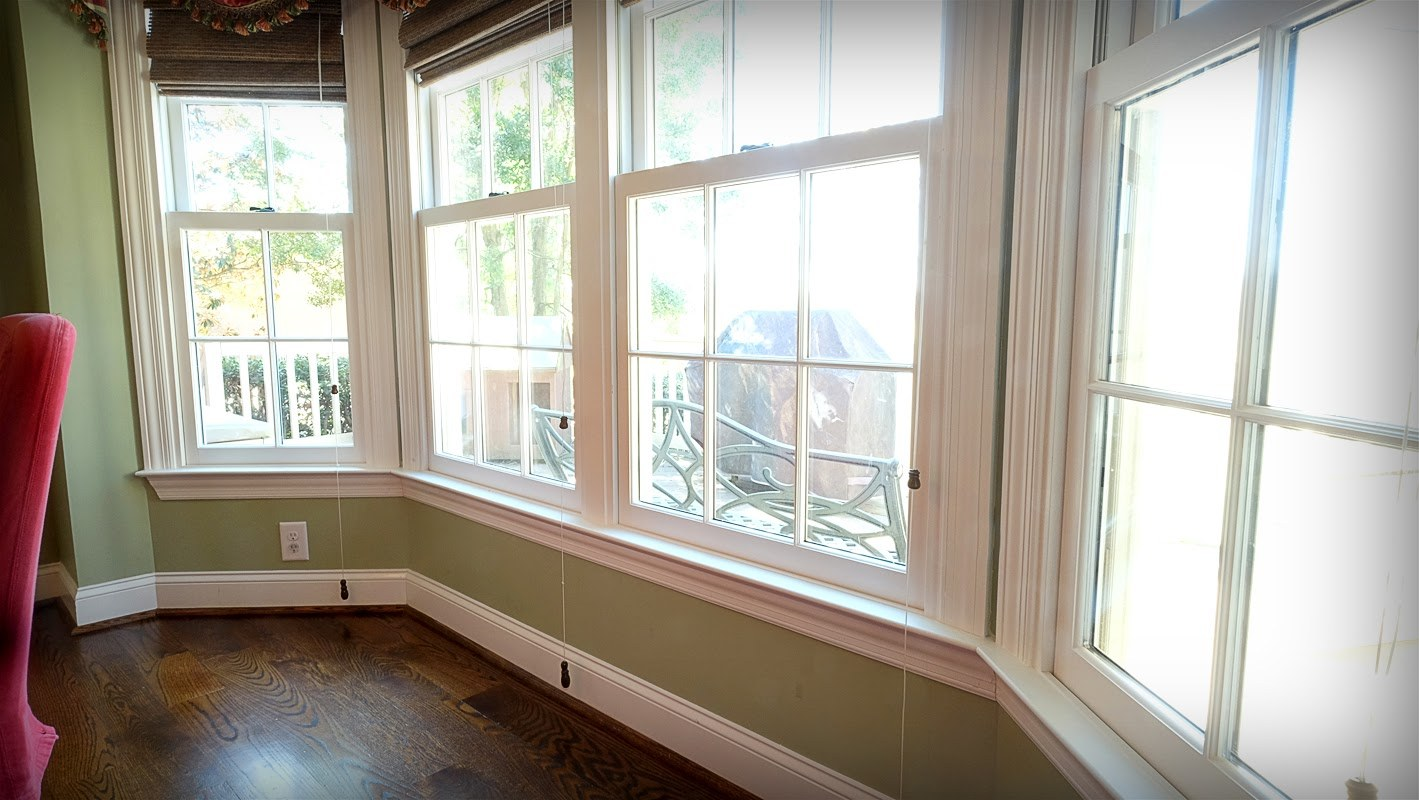 Light green walls, large bay window in dining room looking out on the deck - Residential painting