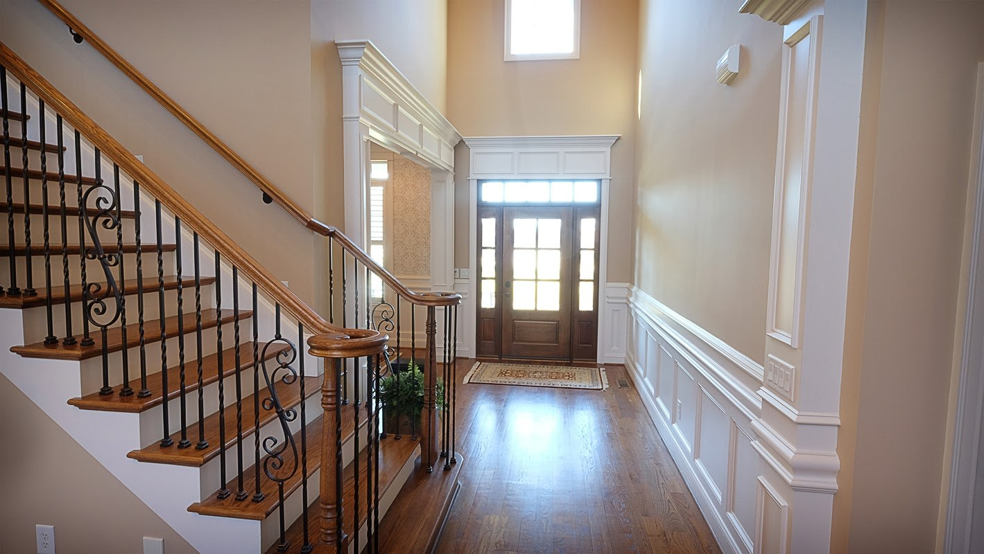 Entry way with vaulted ceilings, white decorative wood trim, staircase and hardwood floors