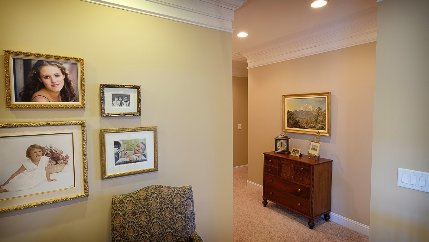 Light tan, taupe, living area with hallway, white trim, crown molding, carpeted floors