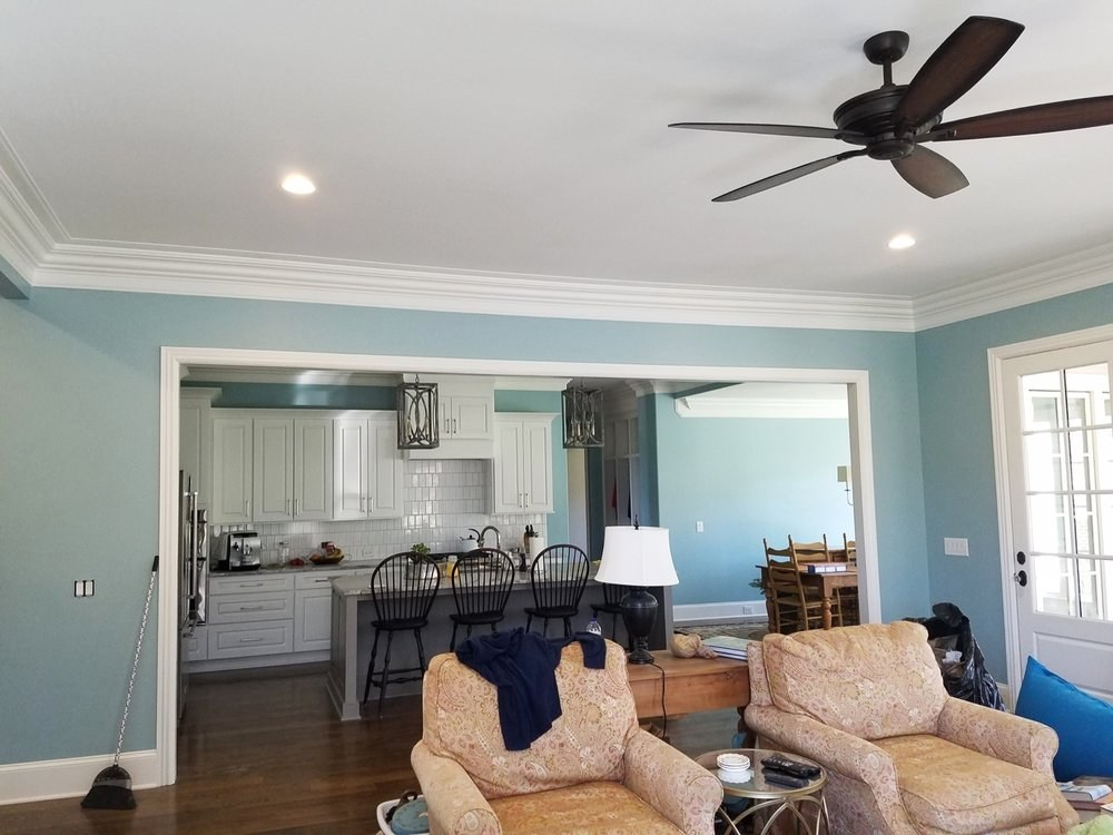 Blue living room and kitchen with white cabinets and trim - Residential painting
