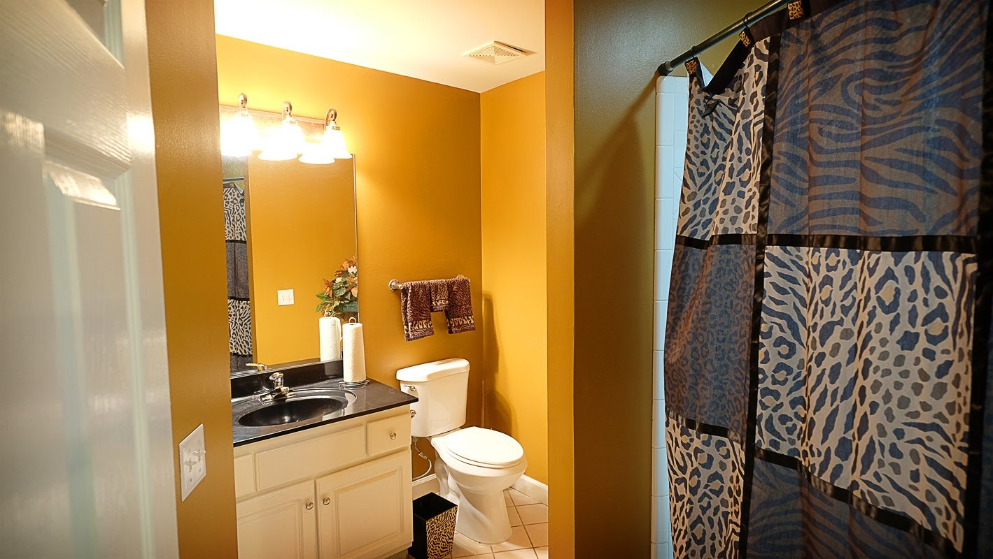 Gold / yellow walls, black and white bathroom vanity and animal print accessories