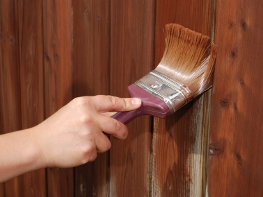 Brush painting a fence brown