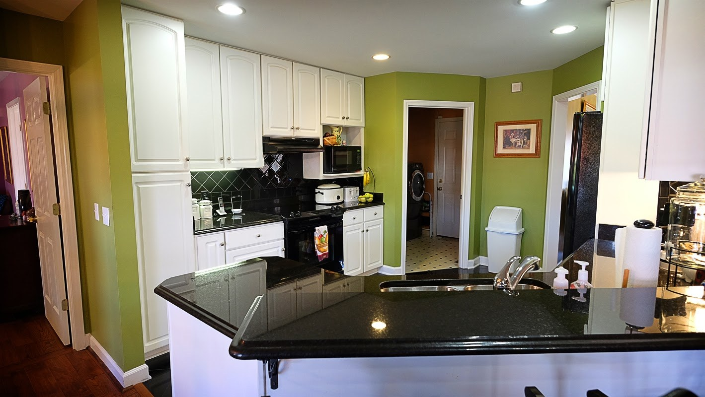 Green and white kitchen with black countertops - Residential painting by Nash Painting Nashville TN